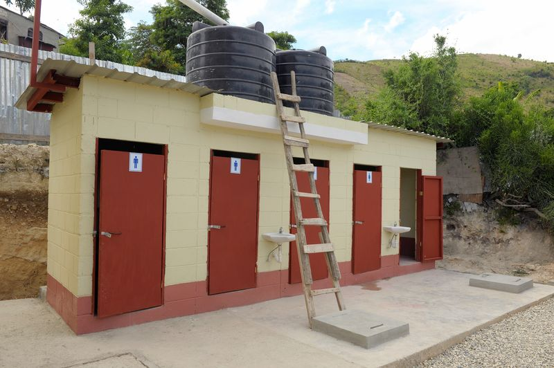 A block of washrooms with red doors.