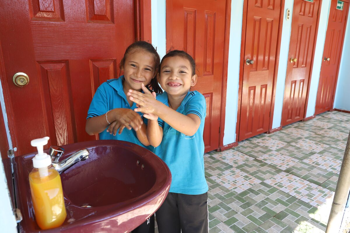 Two girls are wearing blue polo shirts and are both smiling at the camera while washing their hands in a washroom.