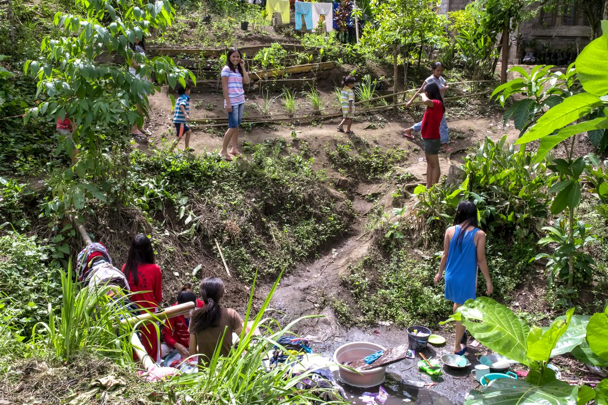 Women gather around a small stream.