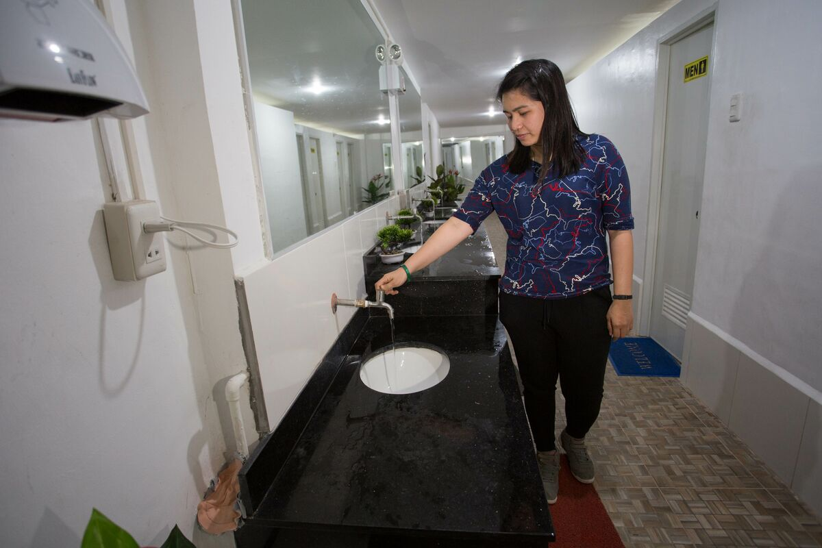 A woman turns on the tap. She is wearing a blue shirt.