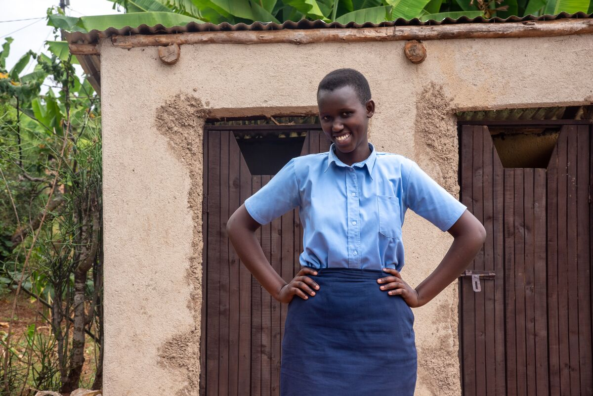 A girl in a blue school uniform stands with her hands on her hips and smiles at the camera.