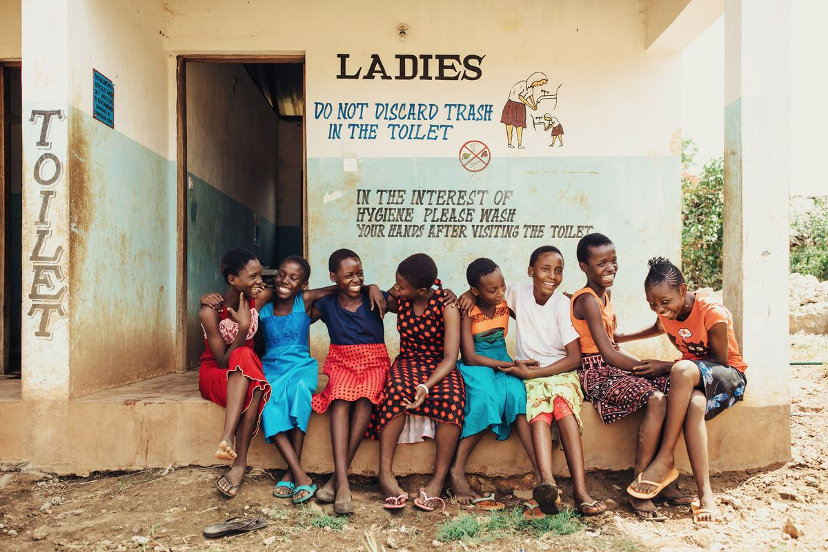 A group of girls sit in a line and laugh together.