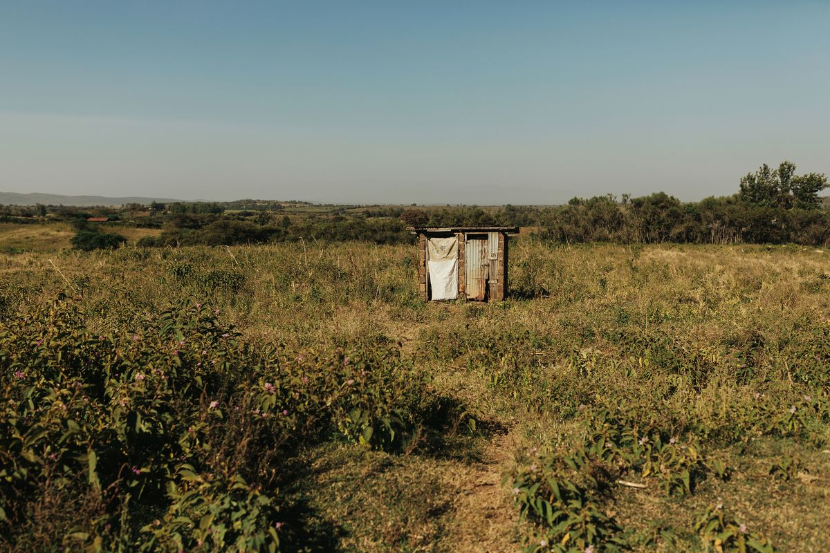 An outhouse in the middle of a field.