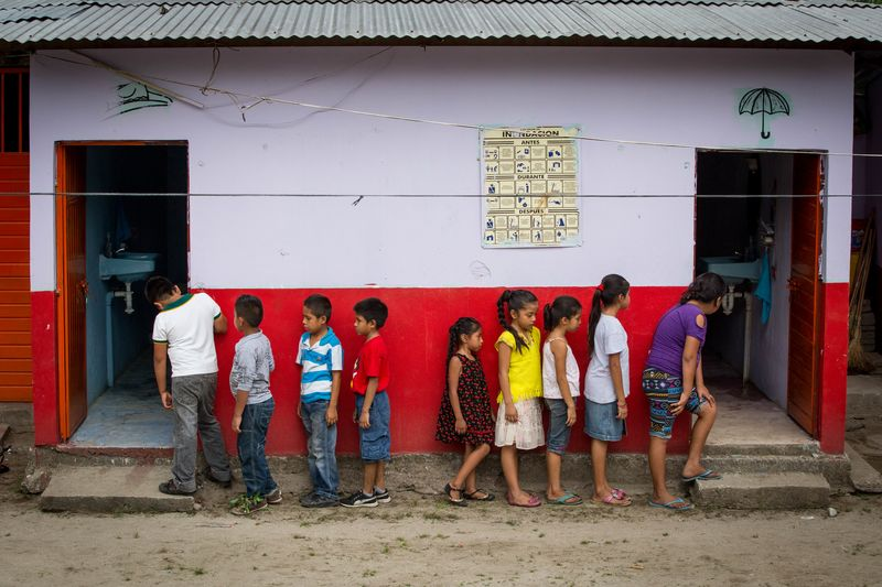 A group of children wait in single file lines outside the white and red painted washrooms.