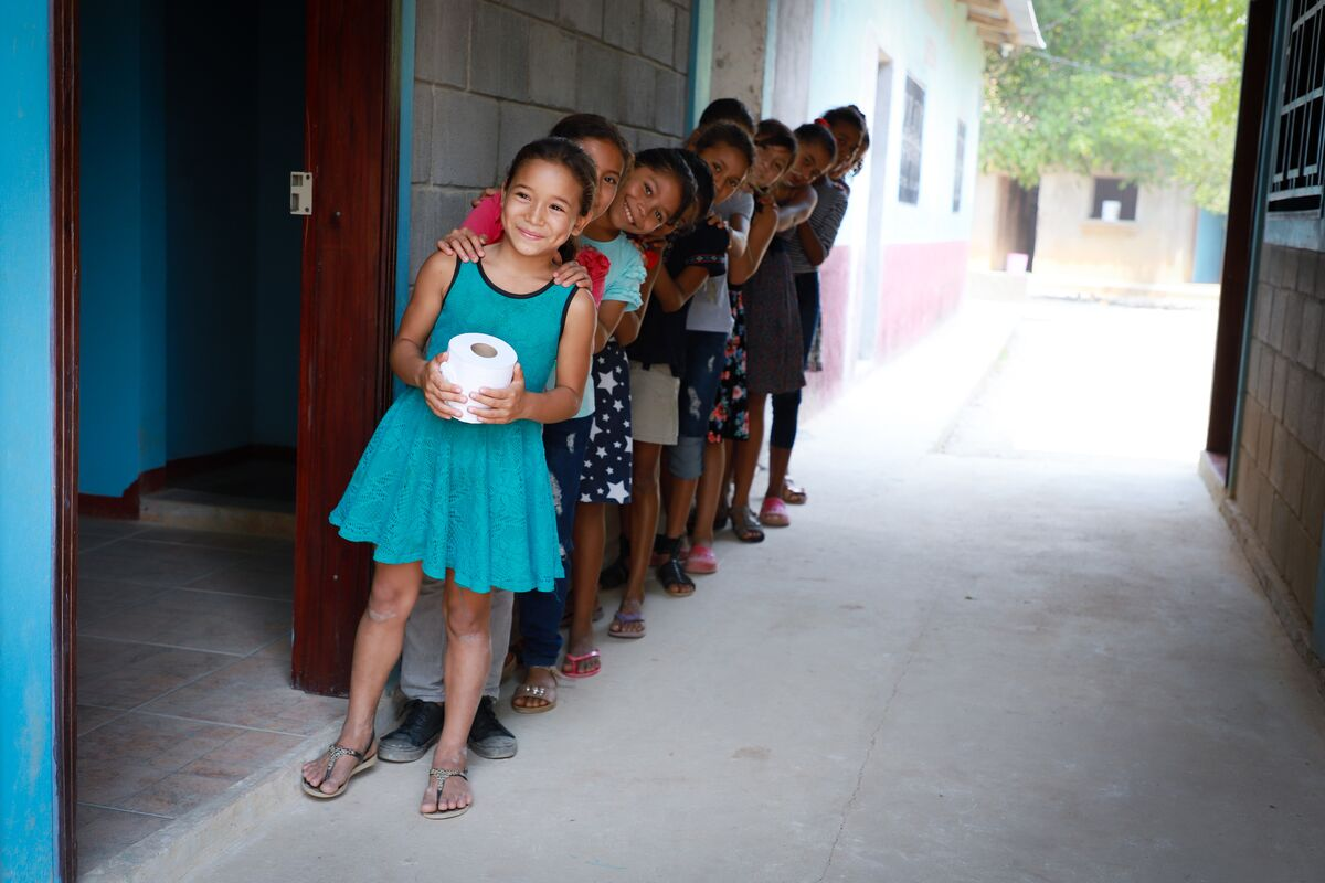 A line of girls stands smiling outside of the washrooms.