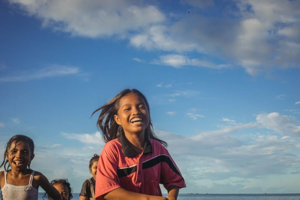 Keilah is wearing a red shirt with a black stripe. She is running along the beach near her home with her friends.