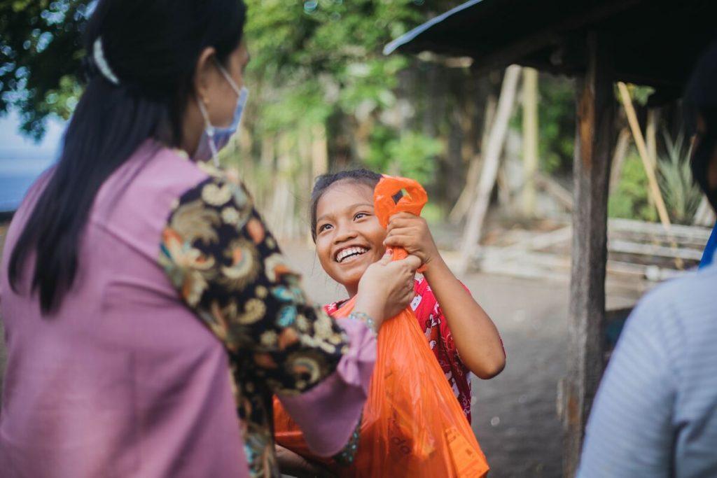 A staff member is handing Keilah an orange bag full of food.