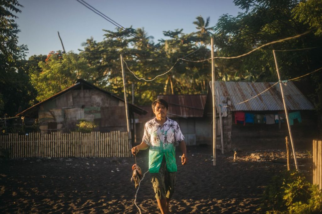 Juandris is carrying fish he caught to the market to sell. There are houses and trees behind him.