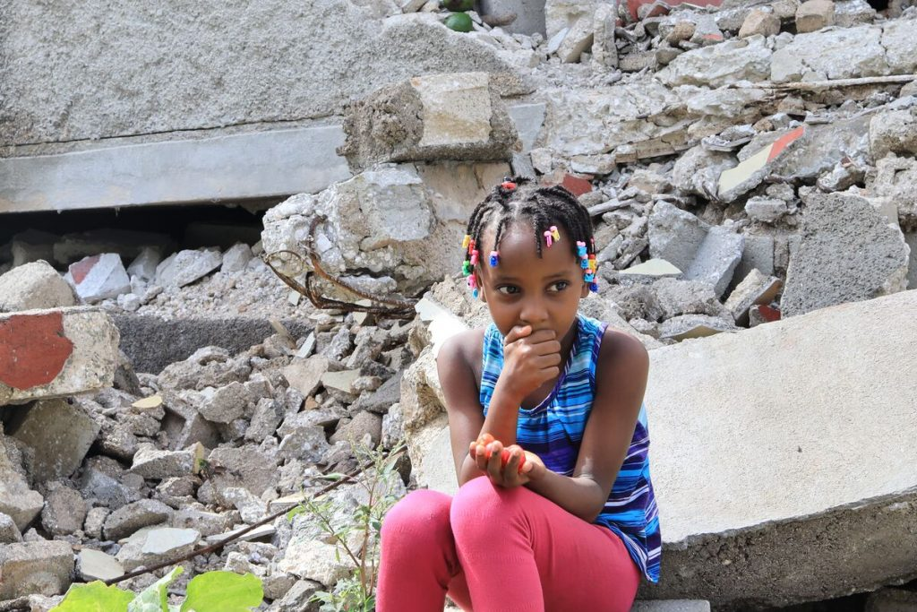 Girl in blue top and red pants sits on a pile of rubble