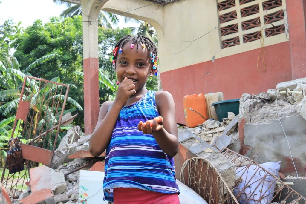 A girl in a blue top stands in front of rubble and holds out her hand
