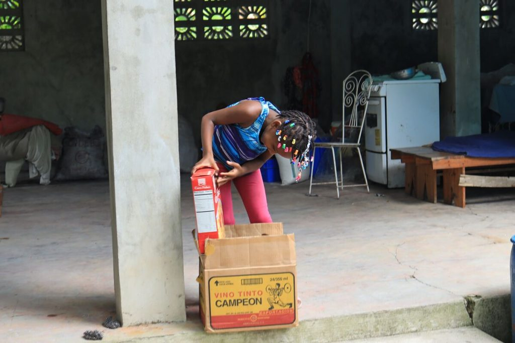 A girl lifts a box of cereal out of a package