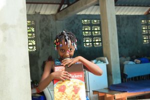 A girl smiles at the camera while holding a box of cereal