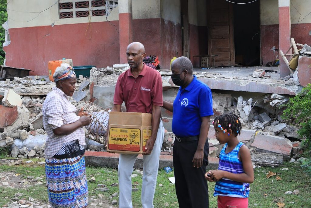 A man in a red shirt carries a box of food to a small group of people