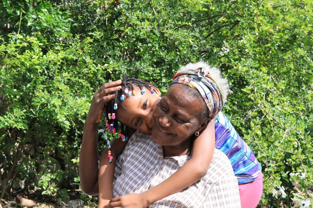 A young girl stands behind her grandmother and kisses her cheek