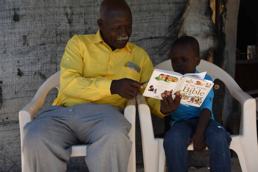 A man in a yellow shirt reads to a child in blue on lawn chairs