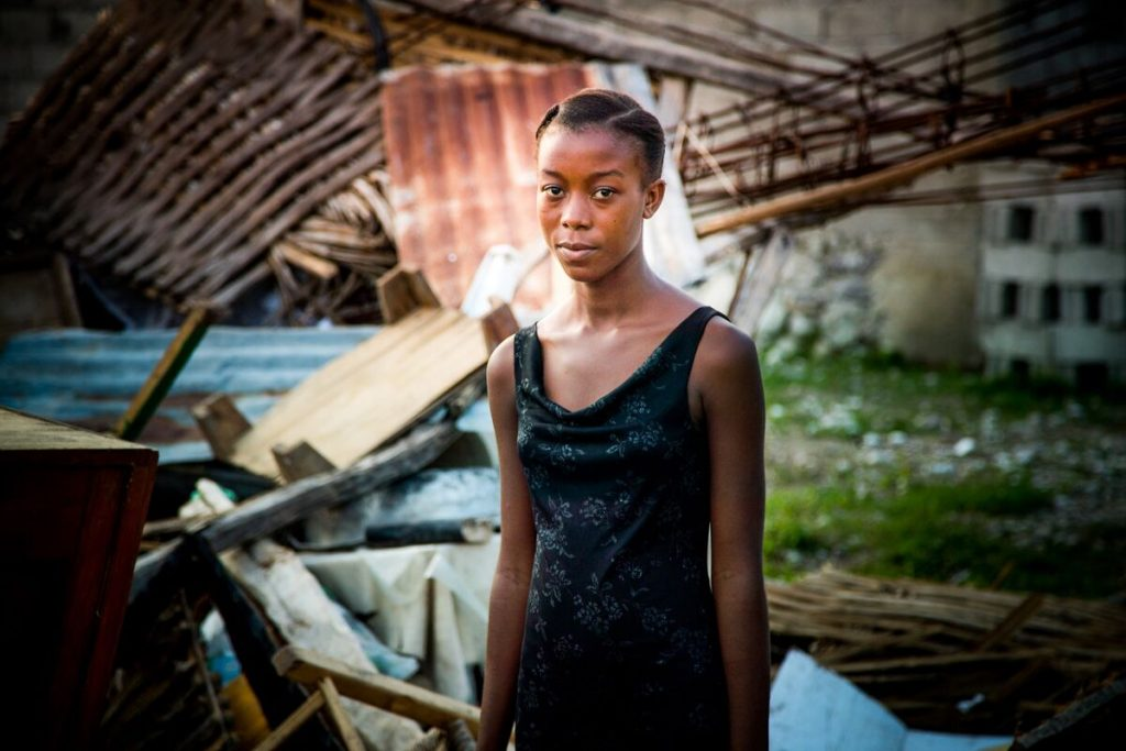 A teenage girl stands in front of a destroyed home