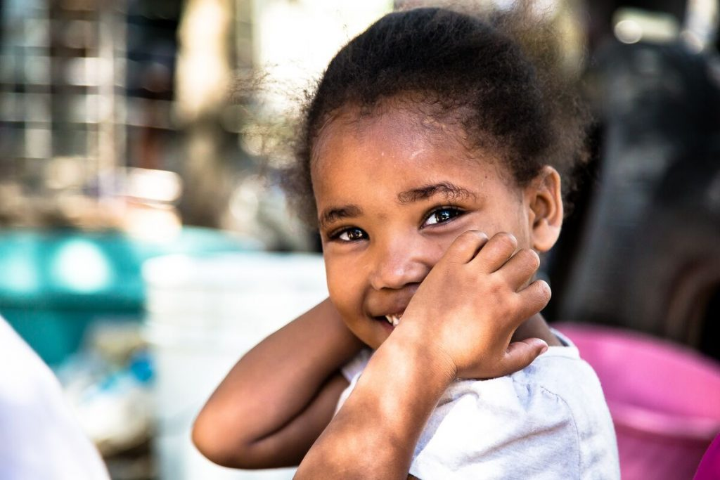 A young girl smiles at the camera with her hands on her face