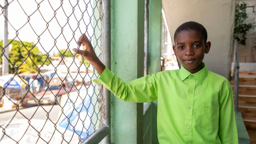 Boy in a green shirt holds onto a fence and looks at the camera
