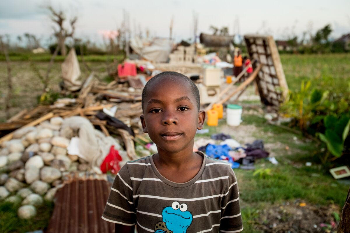 A boy in a brown striped shirt stands in front of rubble