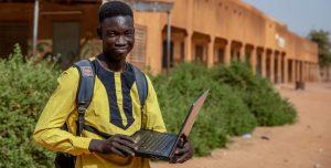 A teenager holds a laptop outside of a Ugandan school.
