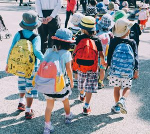 Four kids walk away from the camera wearing backpacks