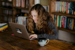 A girl with curly hair smiles at her laptop in front of a bookcase