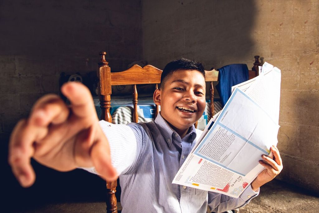 Josué is wearing a blue and white striped shirt. He is sitting in a wooden chair inside his home and is holding letters from his sponsor.