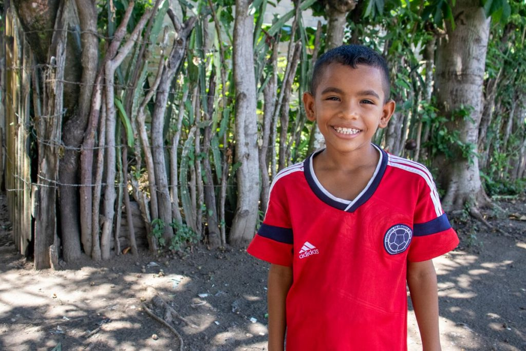 A boy in a red shirt smiles at the camera