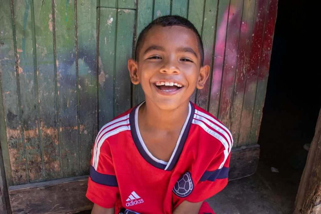 Luis is wearing a red shirt. He is sitting in front of a wooden wall at this home.