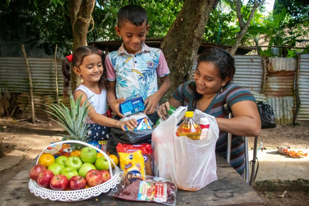 Luis is wearing a blue and white patterned shirt with pink sleeves and jeans. He is in his back yard with his mother and sister. They are looking through food delivered to them by Compassion.