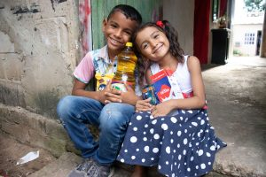 Luis is wearing a blue and white patterned shirt with pink sleeves and jeans. He is sitting outside his home with his sister, María Jose, wearing a blue and white dress. They are each holding food supplies from the centre.