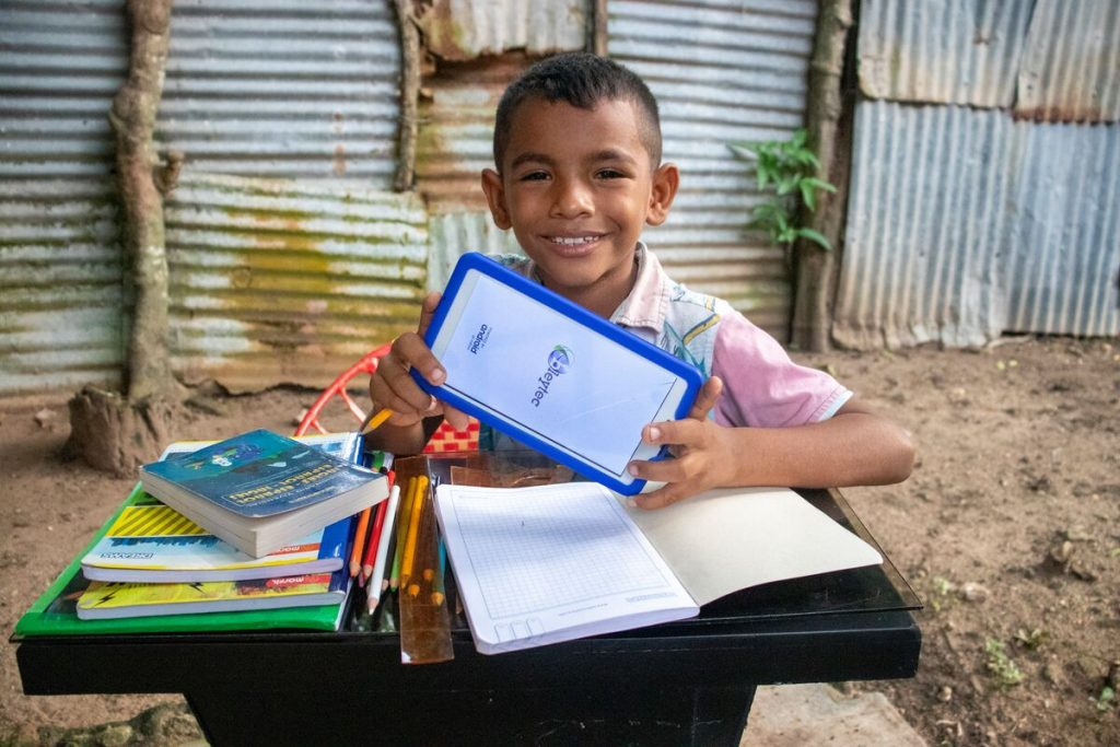 Luis is wearing a blue and white patterned shirt with pink sleeves and jeans. He is sitting at a desk outside his home and is holding a tablet he uses for virtual classes. On the desk in front of him are books, notebooks, and pencils.