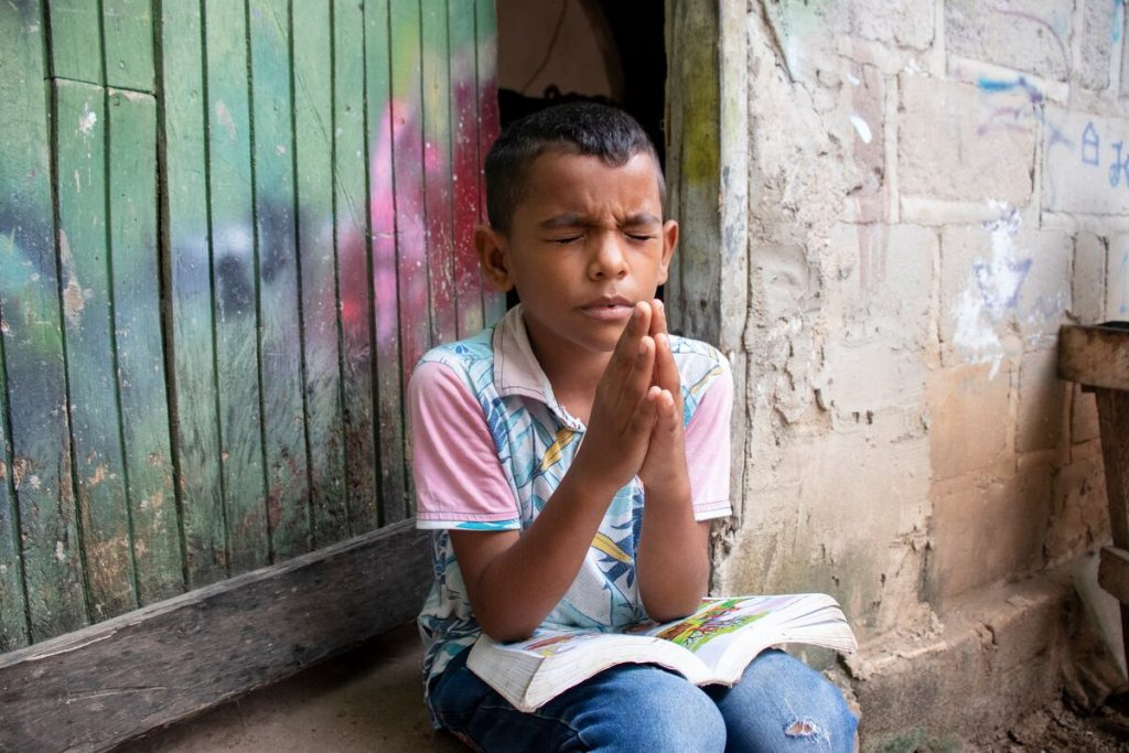 Luis is wearing a blue and white patterned shirt with pink sleeves and jeans. He is sitting outside his home praying with his hands pressed together in front of him. On his lap is his Bible.