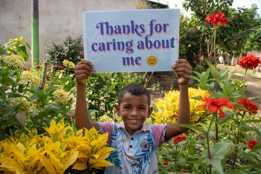 """Luis is wearing a blue and white patterned shirt with pink sleeves and jeans. He is standing outside surrounded by red and yellow flowers. He is holding up a sign that says, """"Thanks for caring about me."""""""