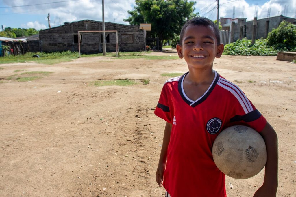 Luis is wearing a red shirt. He is outside on a soccer field and is holding a soccer ball under his arm.