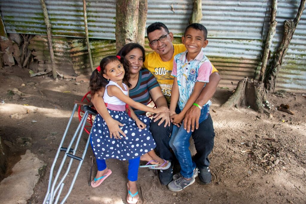 Luis is wearing a blue and white patterned shirt with pink sleeves and jeans. He is sit ting outside his home on his father's lap. Next to them are Luis' mother and sister. There are crutches to the side.