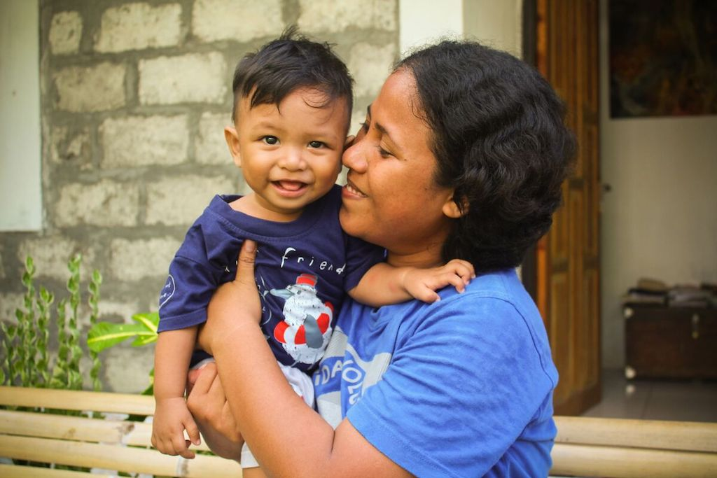 Jeinny is wearing a blue shirt. She is holding her son, Argya, wearing a dark blue shirt, outside their home.