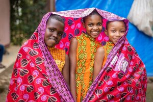 Three girls in orange dresses smile at the camera while wrapped up in a bright pink fabric