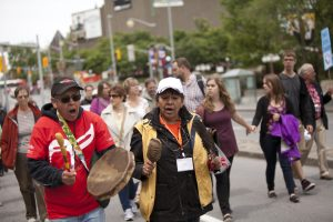 An Indigenous Elder sings and plays a drum during a walk for reconciliation.