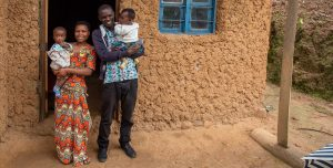 A familt stand infront of a sturdy, simple mud walled home.
