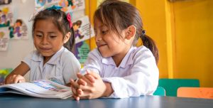 Two young, Mexican girls sit in at a desk in a bright yellow classroom.