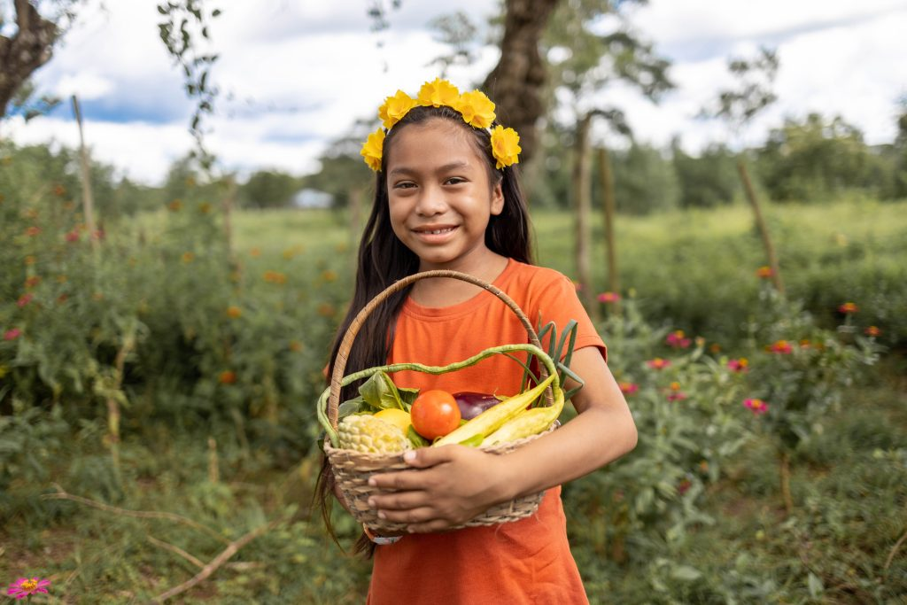 Maira is wearing an orange shirt with jeans. She is holding a basket full of vegetables in a garden.