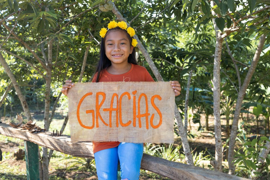 """Maira is wearing an orange shirt with jeans. She is sitting on a fence around her family's garden and is holding a sign that says """"thank you""""."""