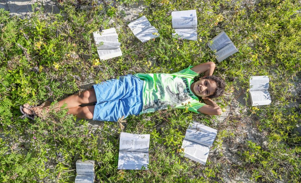 Iarley is laying in the grass, surrounded by Bibles.