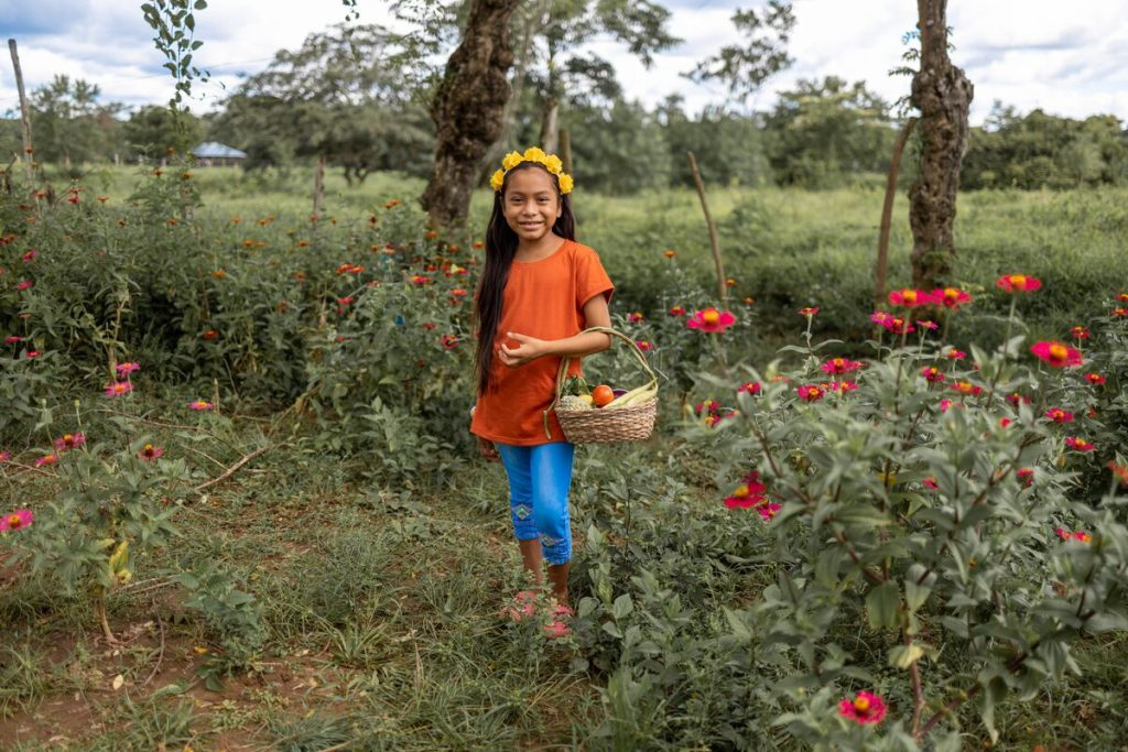Maira is wearing an orange shirt with jeans. She is holding a basket full of vegetables and standing in a garden.