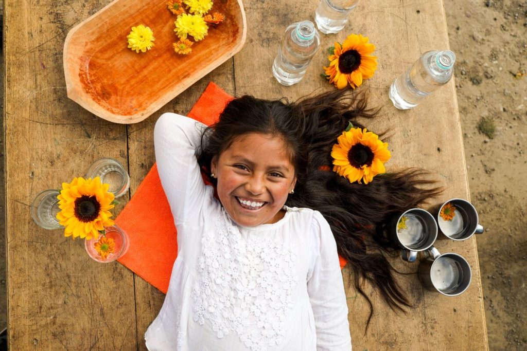 Brittany is laying down on a wooden table, surrounded by flowers and bottles of water.