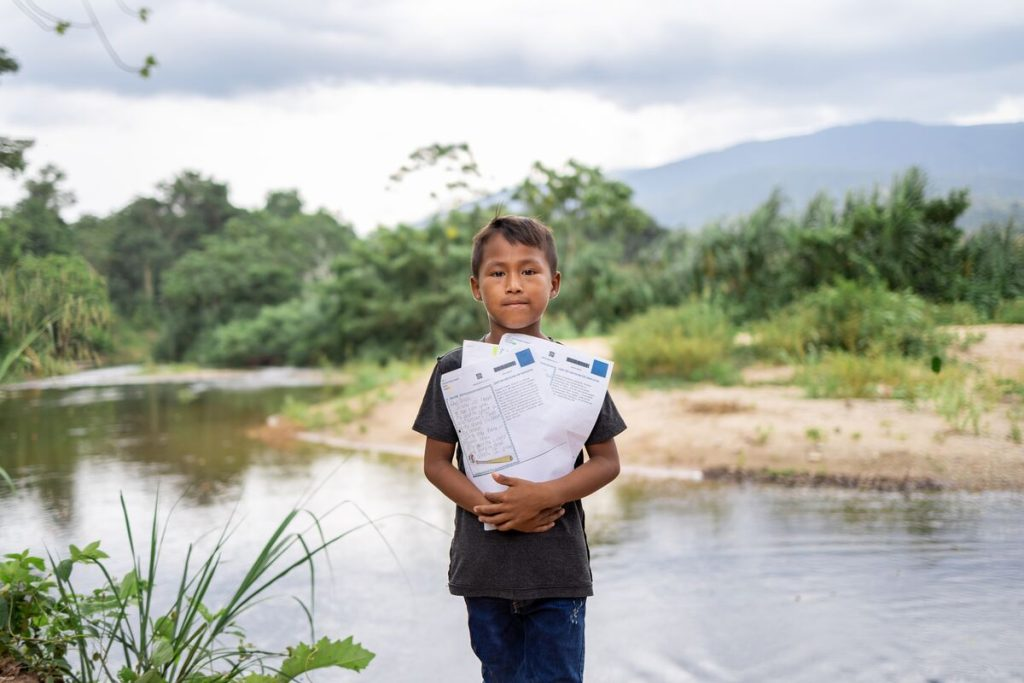 Anllelo is wearing a black shirt and jeans. He is holding several of his sponsor's letters close to his chest. Behind him is a stream.
