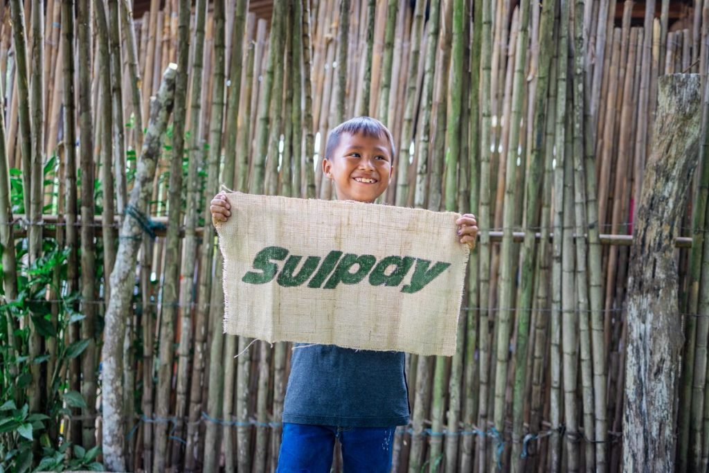 """Anllelo is wearing a blue shirt and jeans. He is standing in front of a bamboo fence and is holding a sign that says, """"Thanks."""""""