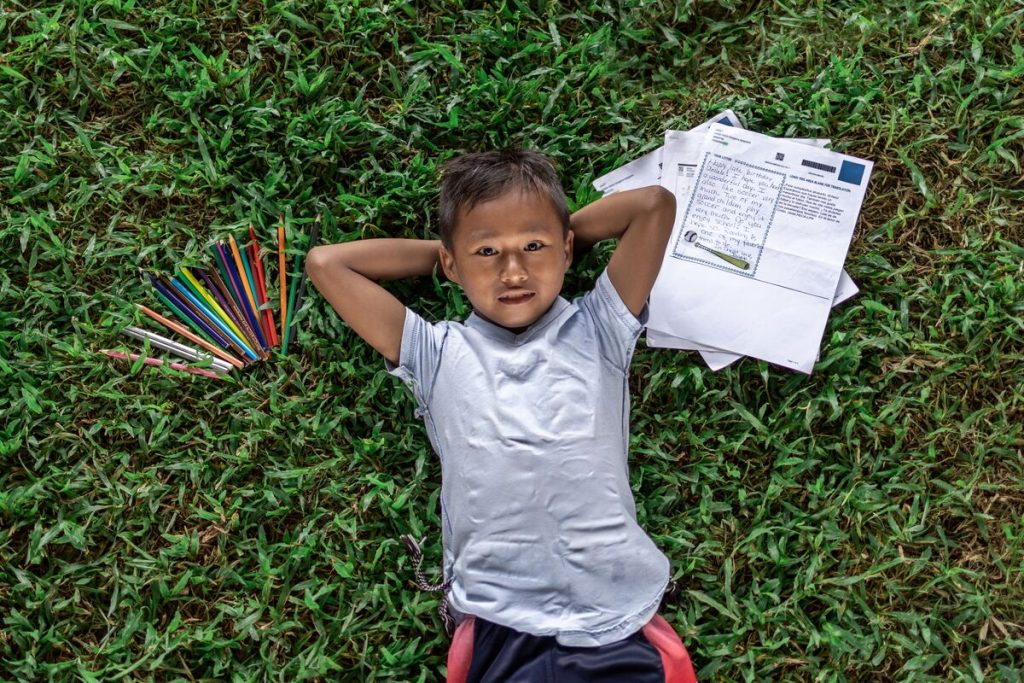 Anllelo is wearing a gray shirt. He is laying down in the grass with his hands behind his head. On one side of him are some of his sponsor's letters. On the other side are colored pencils.