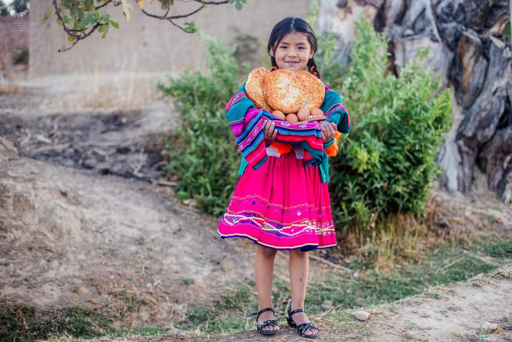 Sheyla is holding a food basket with bread, eggs, and other nutritious food she receives in the food basket the church gives her. She is wearing traditional clothing.